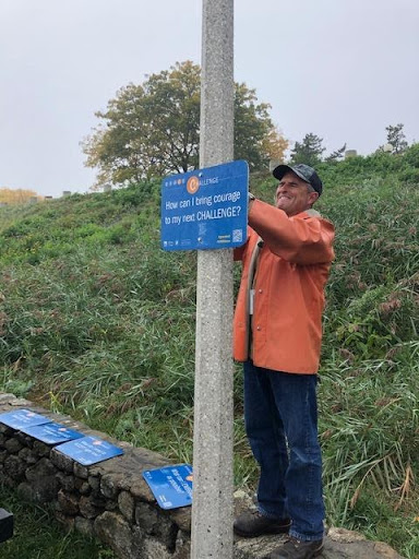 Man in an orange jacket, jeans, and a baseball hat standing on a short wall and installing a sign on a pole.